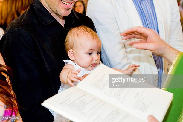 Priest is baptizing little baby in a church.