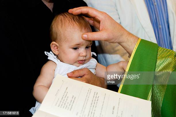 Priest is baptizing little baby in church.
