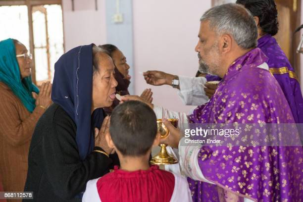 A priest is giving altar bread to a elderly woman with a sari while a ceremony inside a church in Kalimpong
