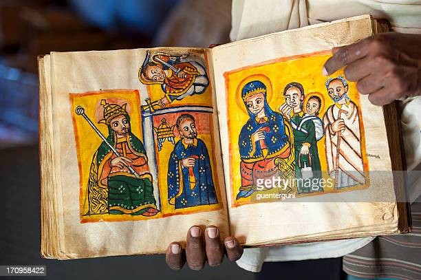 priest is showing an ancient book in ethiopia - axum stock photos and pictures