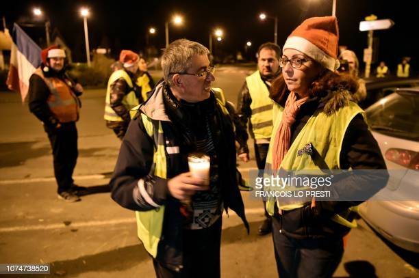 Priest Joseph Nurcho meets yellow vests protestors near a roundabout in Somain northern France where they spend Christmas eve on December 24 2018...