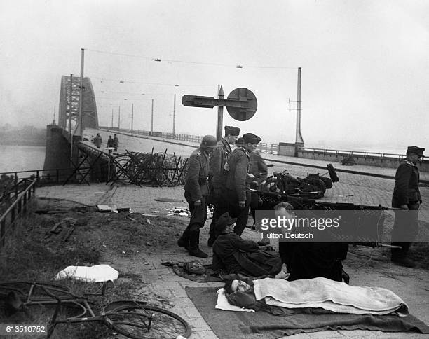 Priest kneels to tend to a wounded German soldier next to Nijmegen Bridge in the Netherlands shortly after the British took the bridge.