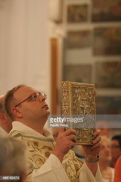 A priest lifts the Holy Bible during an ordination ceremony at Santuario della Madonna dell'Arco