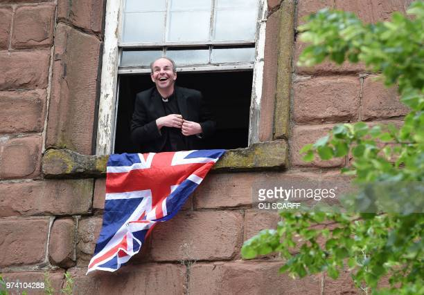 A priest looks out of a window from Chester Cathedral as he waits to see Britain's Queen Elizabeth II and Meghan Duchess of Sussex as they visit...