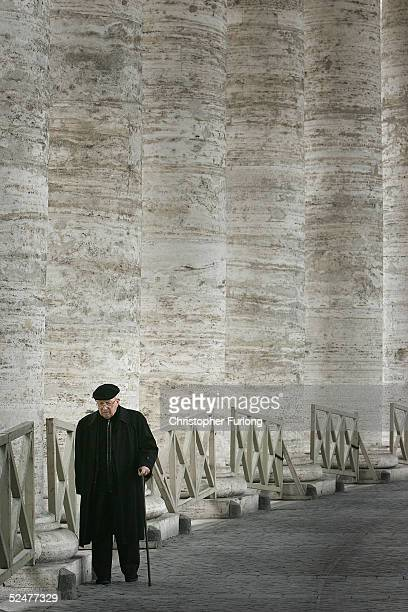 Priest makes his way to morning Mass through the colonnades of St Peter's Square on Good Friday March 2005 in St Peter's Square Vatican City As...