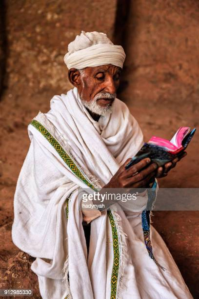 priest of rock-hewn church reading holy book, lalibela - lalibela stock photos and pictures