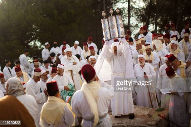 A priest of the ancient Samaritan community wrapped in a prayer shawl holds up a Tora scroll as worshippers pray during the holy day of Shavuot on...
