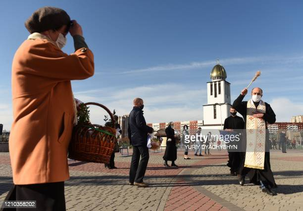 A priest of the Greek Catholic Church with a face mask blesses masked believers holding baskets with Easter eggs and food as they keep social...