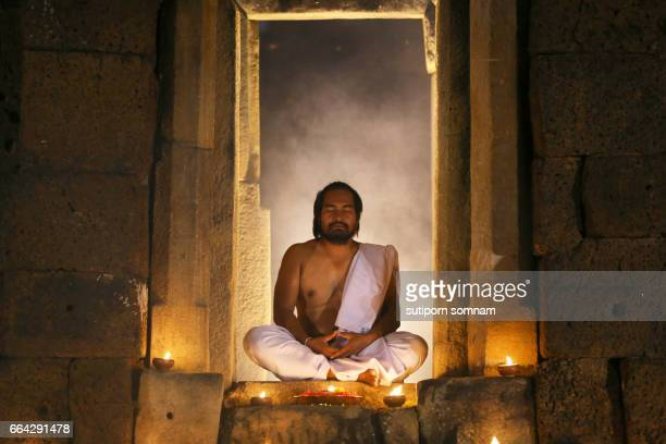Priest or Yogi are sitting meditating in Ancient ornate huts