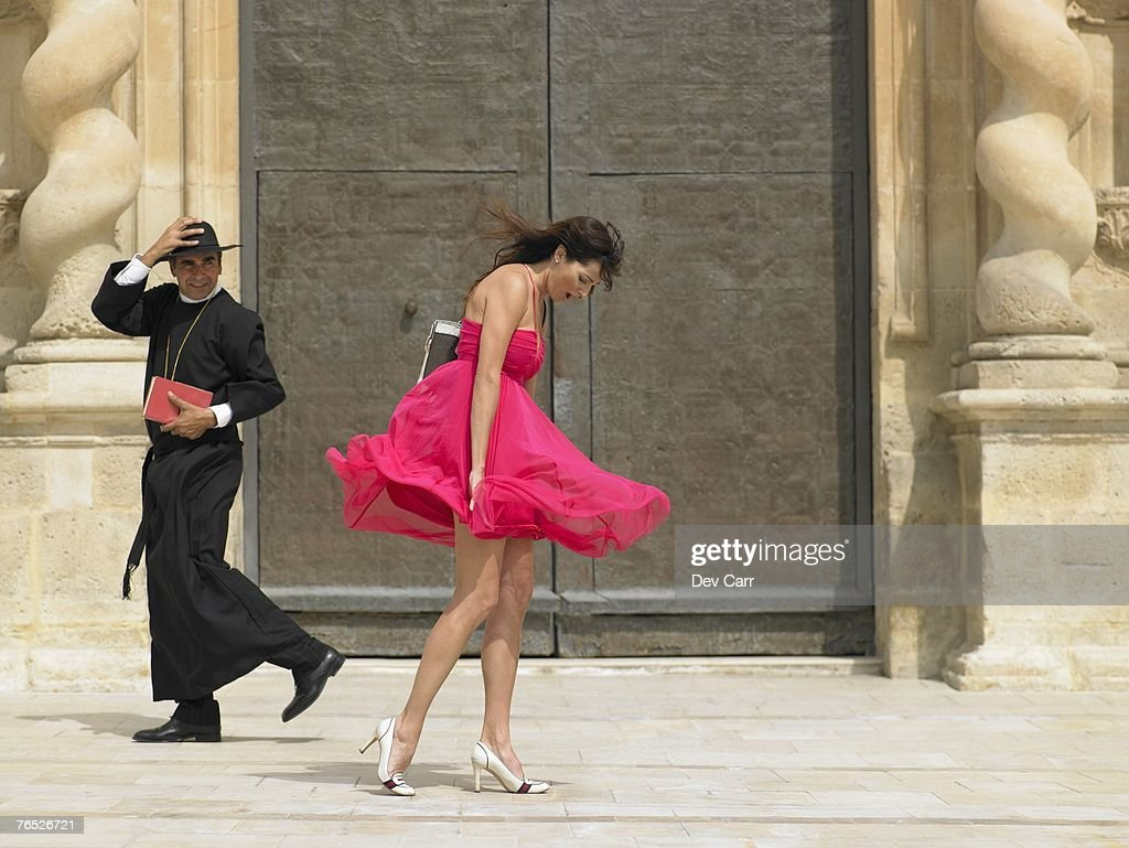 Priest passing woman whose skirt is blowing up in the wind, Alicante, Spain, : Stock Photo