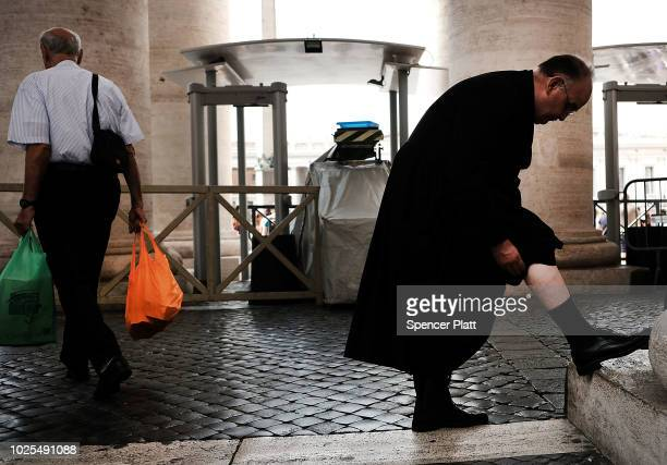 A priest pauses at St Peter's Basilica which is located in the Vatican City and is considered one of the Catholic Church s holiest temples and an...