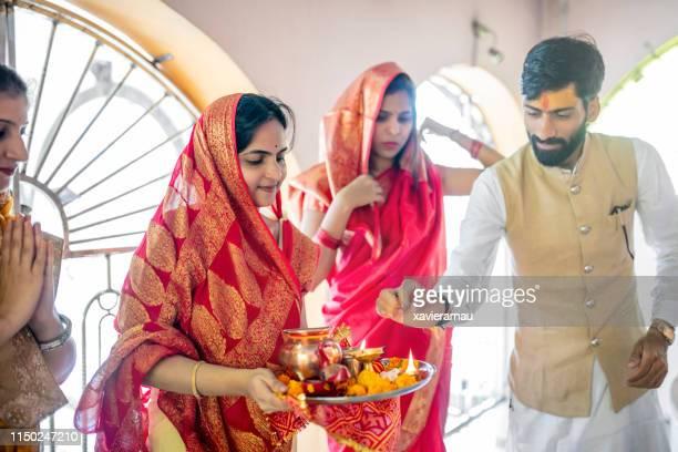 präst som utför bön med familjen i templet - hinduism bildbanksfoton och bilder