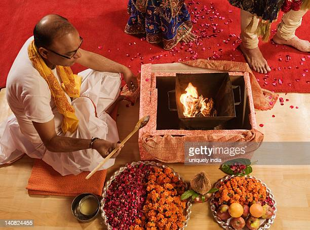 priest performing religious ceremony in wedding mandap - hinduism stock pictures, royalty-free photos & images