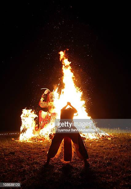 A priest performs prayers at a burning statue of the Chinese deity Da Shi Ye or Guardian God of Ghosts during the Chinese Hungry Ghost Festival on...