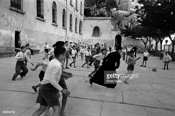 A priest playing a nifty game of football with young boys in the courtyard of an orphanage Salerno Italy In black and white book