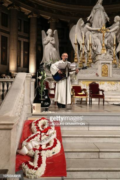 A priest plays guitar during a mass in tribute to French rock singer Johnny Hallyday in Paris on December 9 2018 one year after Johnny's death French...