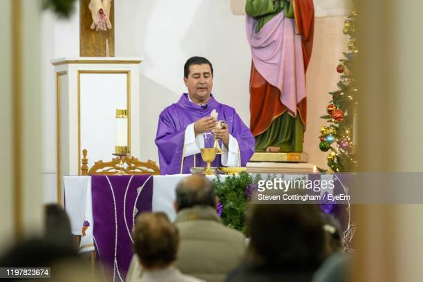 priest praying in church - steven cottingham stock-fotos und bilder