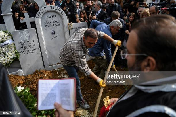 Priest prays as mourners bury Turkish photographer Ara Guler's coffin at Sisli Armenian cemetery during his funeral at Sisli district in Istanbul on...