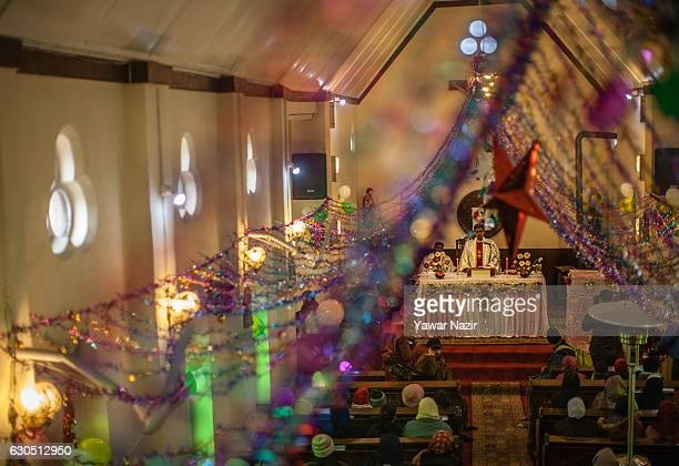A priest prays in the Holy Family Catholic Church during Christmas on December 25 2016 in Srinagar the summer capital of Indian administered Kashmir...