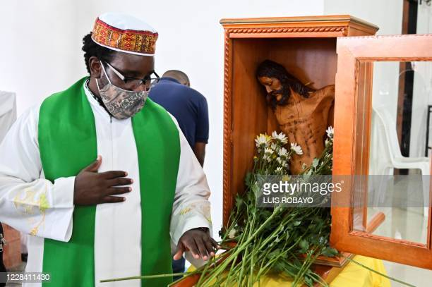 A priest prays next to Christ mutilated of Bojaya on September 8 2020 in Cali Colombia during a pilgrimage to various cities for the week of peace...