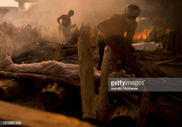 Priest prepares to perform the last rites of a patient who died of COVID-19 during a mass cremation at a crematorium on May 01, 2021 in New Delhi,...