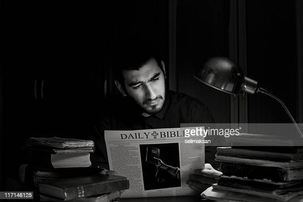 priest reading daily bible newspaper in dark. - bible photos stock pictures, royalty-free photos & images