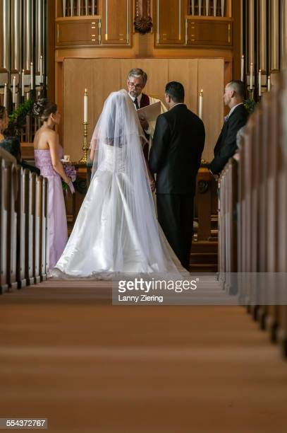 Priest reading to bride and groom in wedding ceremony