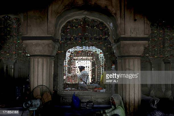 A priest reads the Sikh holy book the Guru Granth Sahib while pilgrims gather at a shrine in Lahore on June 29 on the 174th death anniversary of...