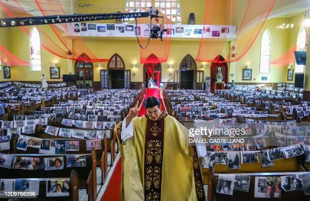 TOPSHOT Priest Reginaldo Manzotti of the Nossa Senhora de Guadalupe sanctuary streams his Easter sunday service with printed photos of his...