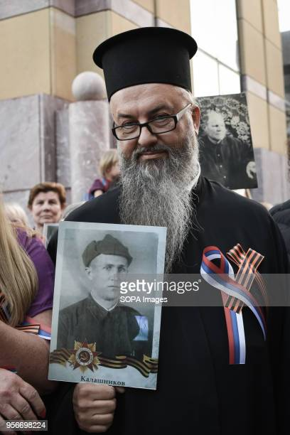 A priest seen holding an old photograph during The Immortal Regiment march Thousands of Russian citizens participated in the celebrations for the...