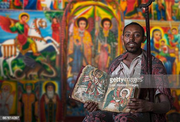 priest showing an ancient religious book in an orthodox monastery, tigray, ethiopia - tigray stock photos and pictures
