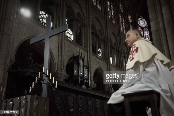 A priest sits near a cross during a ceremony held to present to to faithfuls the Crown of Thorns a relic of the passion of Christ at the NotreDame...