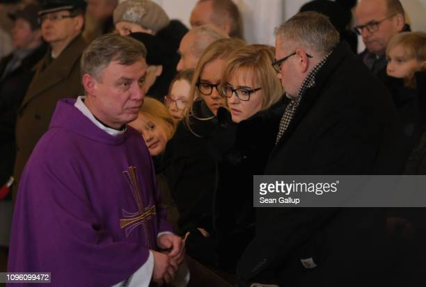 A priest speaks with family members of murdered Gdansk mayor Pawel Adamowicz including his wife Magdalena and his brother Antonina during a Catholic...