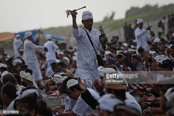 A priest splash holly water to Hindus devotees as they pray during the Melasti ritual ceremony at Parangkusumo beach on March 28 2014 in Yogyakarta...