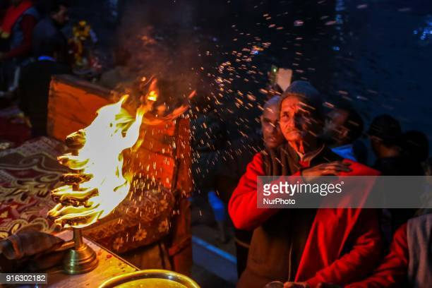 Priest splatter holy water drops to devotess after Goddess Ganga aarti ' Paryer' at Har ki Pauri in Haridwar Uttrakhand India on 8th Feb 2018 The...