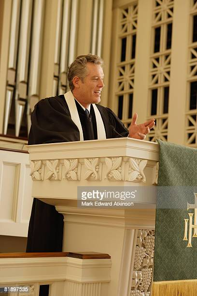 priest standing at pulpit - vicar stock pictures, royalty-free photos & images