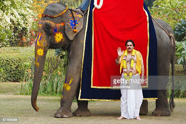 priest standing beside an elephant - prayer pose greeting bildbanksfoton och bilder