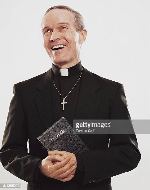 priest standing holding bible with joy - priest stock pictures, royalty-free photos & images