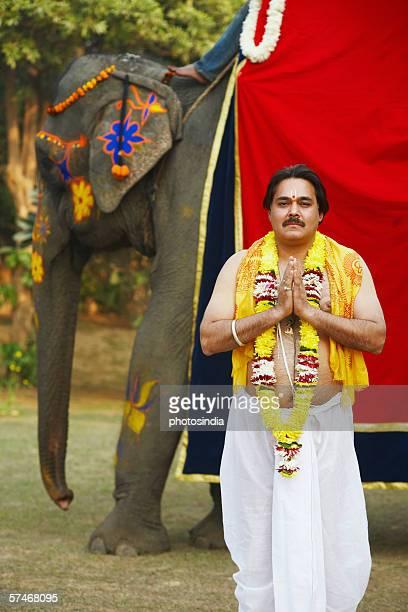 priest standing in a prayer position beside an elephant - prayer pose greeting bildbanksfoton och bilder