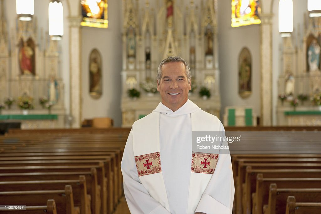 Priest standing in ornate church : ストックフォト