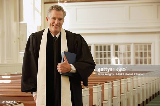 Priest standing next to pews
