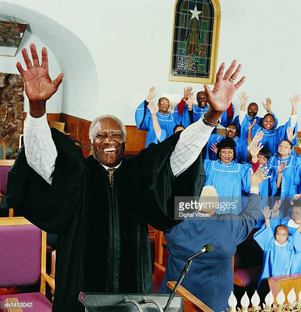 priest standing on a pulpit with his arms upraised in front of a gospel singing choir - gospel stock photos and pictures