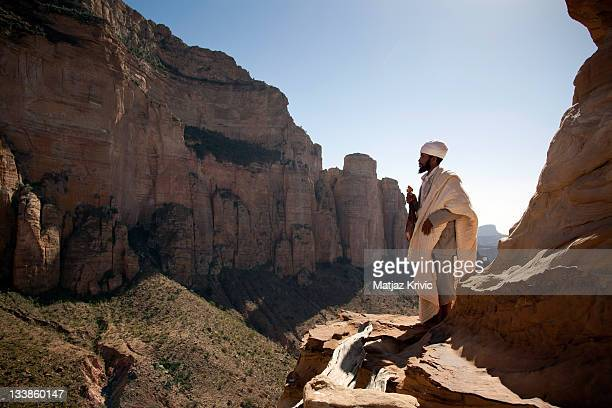 Priest standing on the edge of a cliff in front of the entrance to Ethiopian Orthodox roch hewn church of Abuna Yemata Guh in Gheralta Cluster Tigrey...