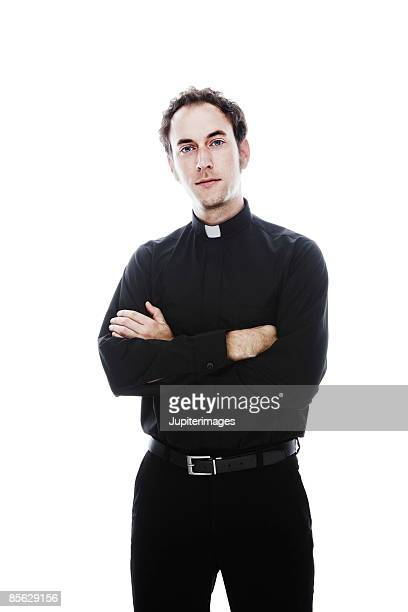 Priest standing with arms folded