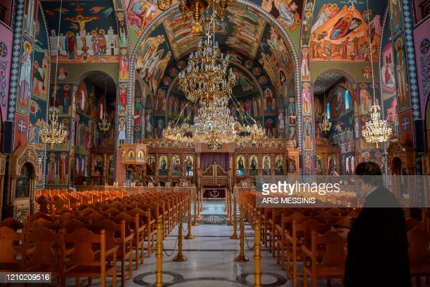 A priest stands inside an empty Orthodox church during the Holy Friday celebrations on April 17 in Athens Easter is Greece's foremost religious...