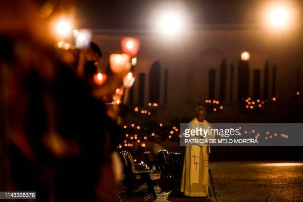 Priest stands next to pilgrims holding candles as they pray during the candle procession at the Fatima shrine in Fatima, central Portugal, on May 12,...