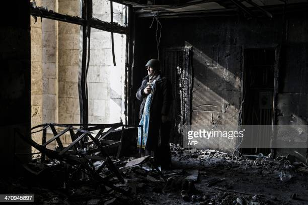 A priest stands on February 21 2014 in the ruins of Kiev's Trade Union building Ukraine's parliament on February 21 voted to return the exSoviet...