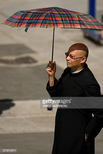 A priest stands under an umbrella as Pope Benedict XVI celebrates a mass the Almudena Cathedral during the World Youth Day festivities in Madrid on...