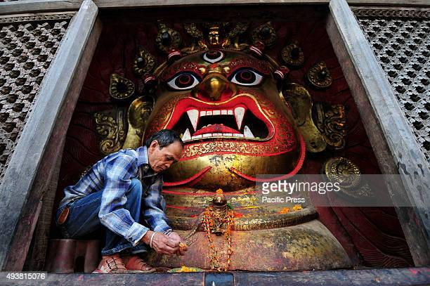 A priest stays in front of idol Swet Bhairav to offer holy flowers towards devotees on the occasion of Navami 9th day of Dashain Festival at...