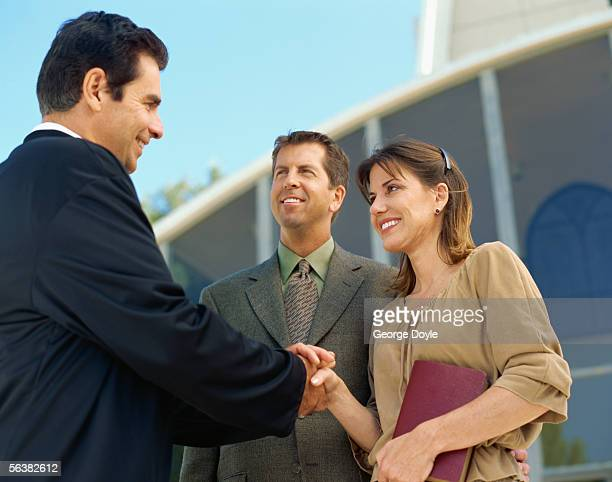 priest talking to a mid adult couple